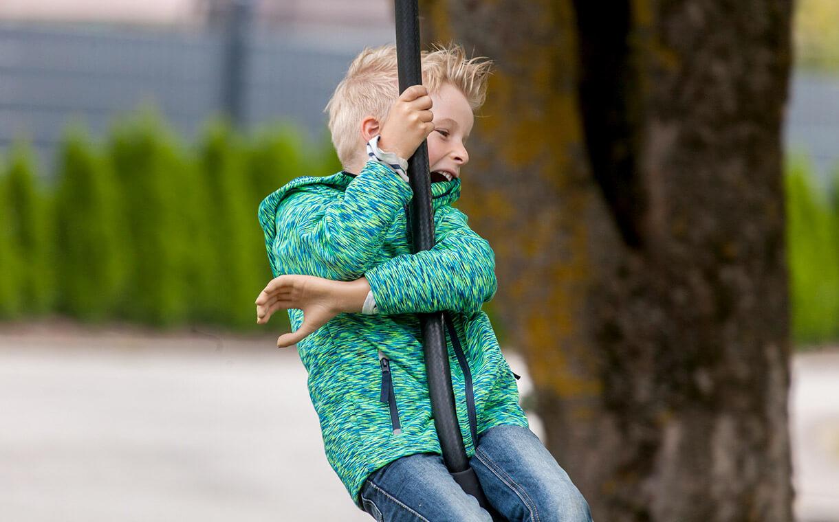 Ein Junge schwingt freudig auf einer Seilbahn