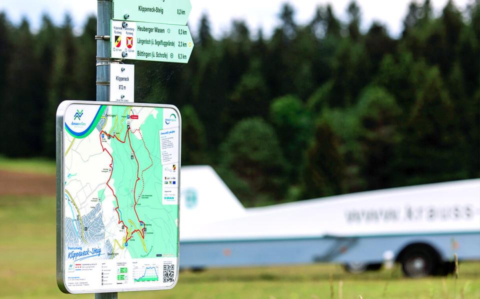 Schild des Klippen-Streig-Wegs mit einem Segelflugzeug und Wald im Hintergrund